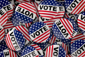 "pile of American flag pins that say, ""vots"""
