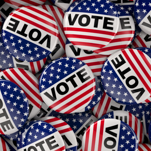 """pile of American flag pins that say, """"vots"""""""